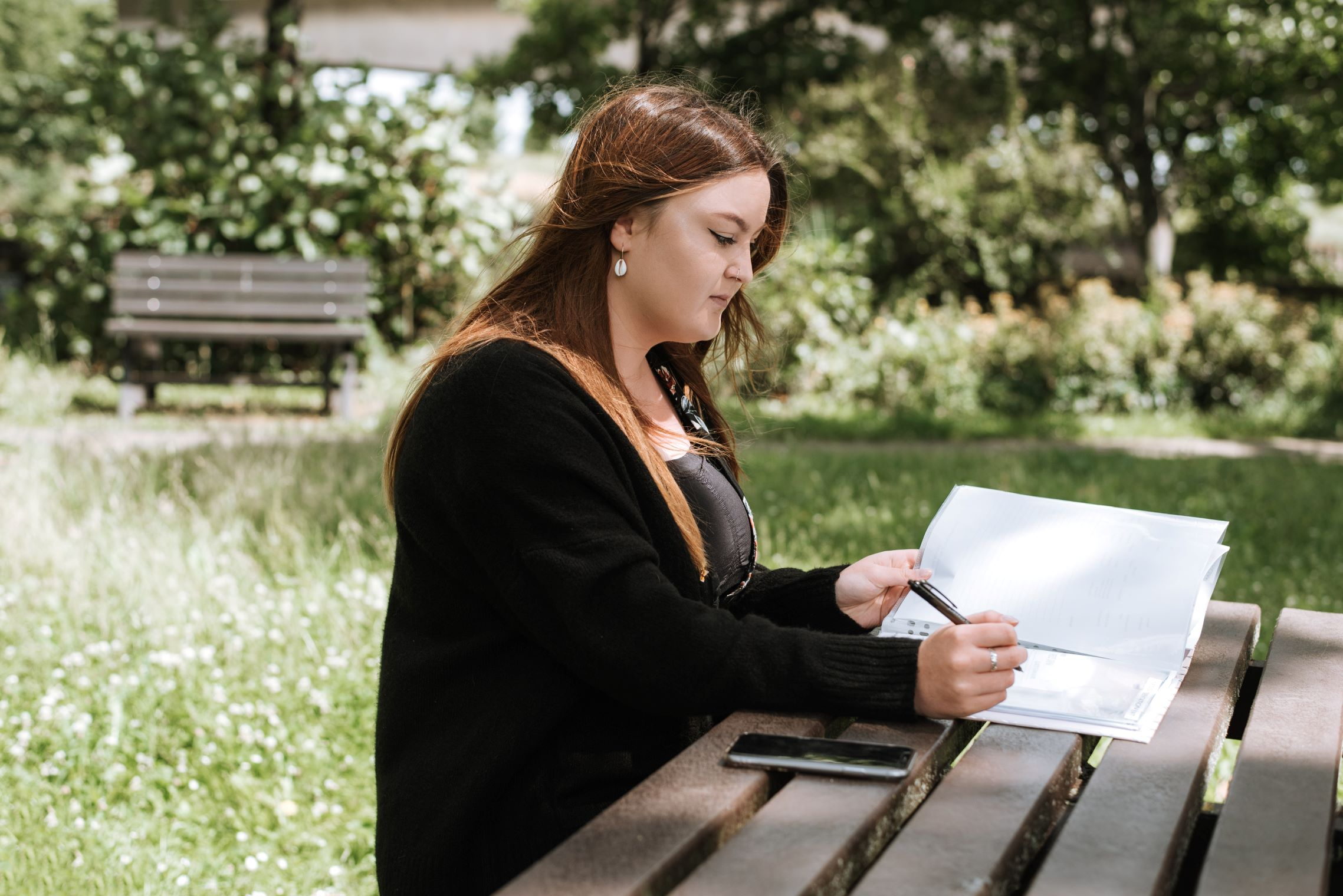 estate planning mistakes ot avoid woman writing in notebook with phone in park