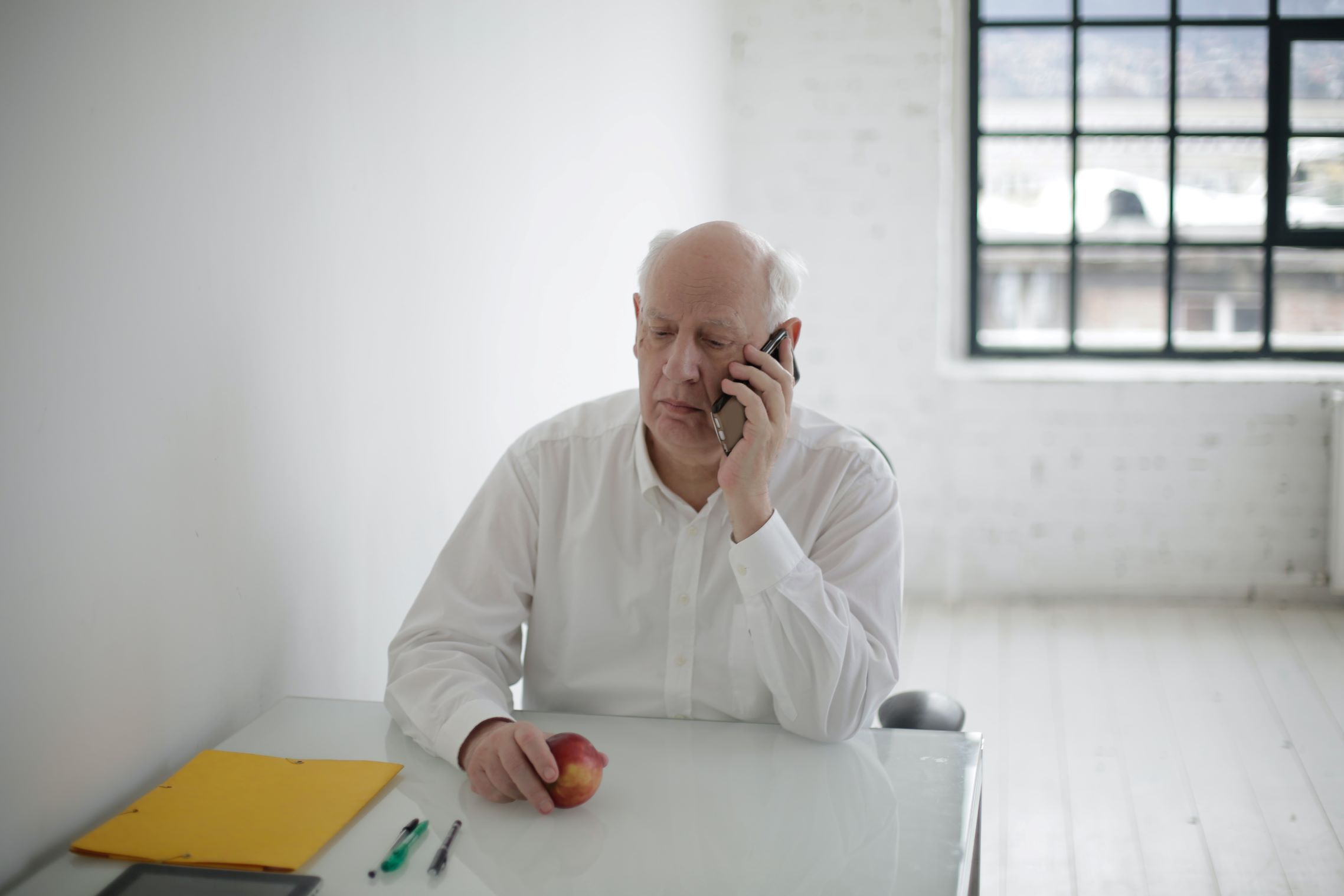 senior man on phone scammer call covid-19 apple at table